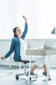 Fotografie happy girl in earphones raising hand and looking away while using laptop at desk