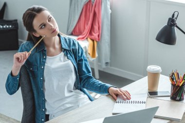 pensive girl holding pencil and looking away while studying at home