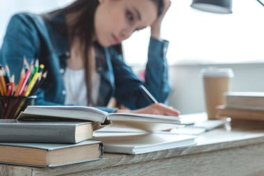 close-up view of books on desk and girl taking notes behind