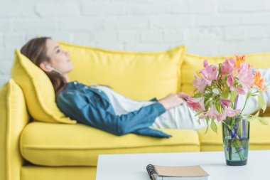 notebook and flowers in vase on table and girl listening music in earphones on sofa behind