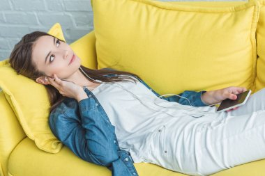 pensive smiling girl holding smartphone and listening music in earphones while lying on sofa and looking up