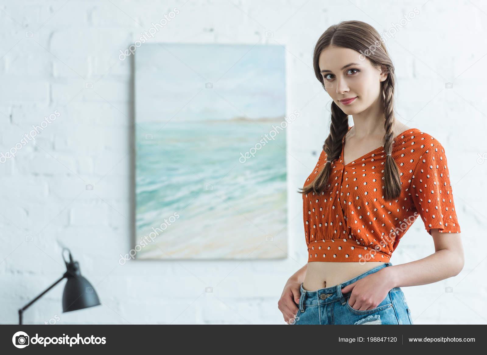 Mooie tiener meisje met vlechten staan kamer met schilderen muur