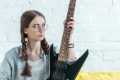 Fotografia bella ragazza teenager che si siede sul divano con la chitarra elettrica