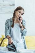 Fotografie Teen Mädchen sprechen auf Smartphone beim Bügeln ihrer Kleidung