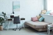 pohovka s polštáři a tabulku s notebookem v obývacím pokoji