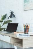 Fotografia computer portatile, libri, lampada e matite sul tavolo per lavoro a distanza