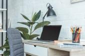 přenosný počítač s prázdná obrazovka, knihy, lampy a tužky na stole v domácí kanceláři