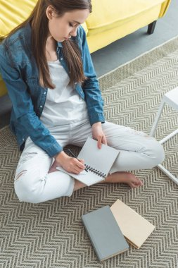 high angle view of girl writing in notebook while sitting on carpet and studying at home
