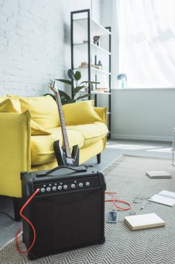electric guitar and loud speaker with smartphone standing on floor with books near sofa