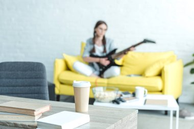 girl playing electric guitar on sofa, boks and disposable cup of coffee on table on foreground