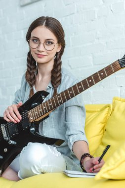 beautiful teen girl with electric guitar writing song in textbook