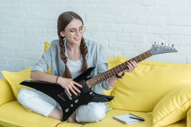 smiling teen girl playing electric guitar while sitting on yellow sofa with textbook