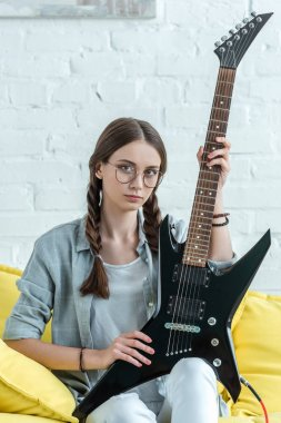 attractive teen girl sitting on sofa with electric guitar