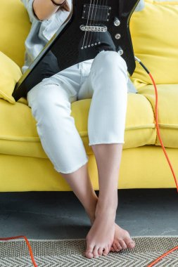 cropped view of girl sitting on yellow sofa with electric guitar