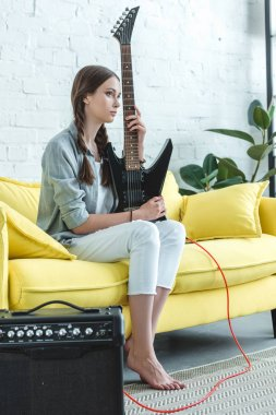 teen girl sitting on sofa with electric guitar and loud speaker