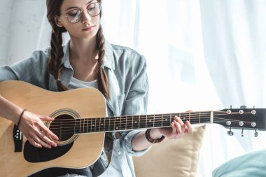 attractive teen girl playing acoustic guitar