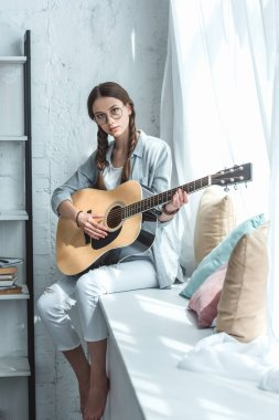 teen girl playing acoustic guitar while sitting on windowsill