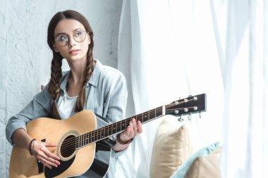 beautiful teen girl playing acoustic guitar near window