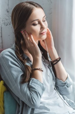 attractive teen girl with closed eyes listening music with earphones