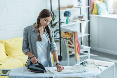 beautiful young woman ironing white pants at home
