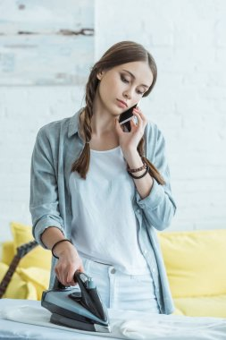 teen girl talking on smartphone while ironing her clothes