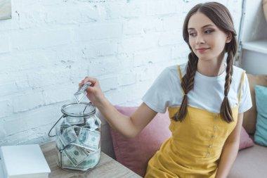 beautiful teen girl putting dollar banknote into saving glass jar