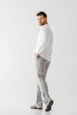 young handsome man in linen clothes posing isolated on grey background