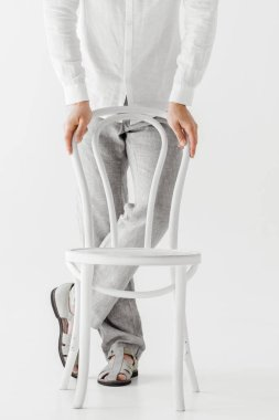 cropped image of male model in linen clothes standing near chair isolated on grey background