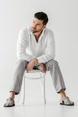 confident man in linen clothes sitting on chair and looking away isolated on grey background