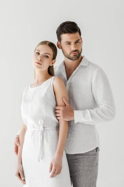 handsome man in linen clothes embracing girlfriend isolated on grey background