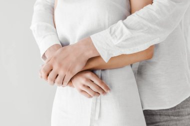 cropped image of man in linen clothes embracing girlfriend isolated on grey background