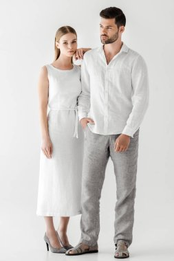 young woman in linen white dress embracing boyfriend with hand in pocket isolated on grey background