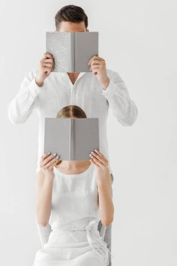 couple in linen clothes covering faces by books isolated on grey background