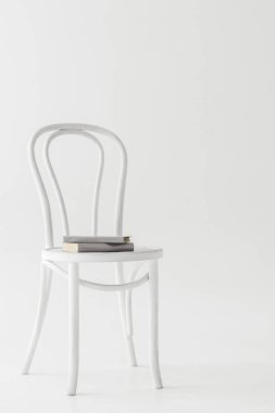 front view of chair with two books isolated on grey background