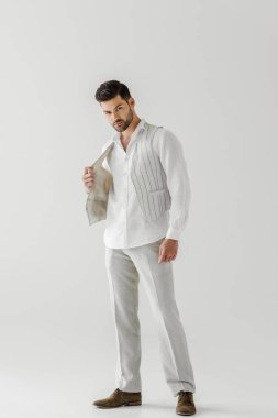 handsome man in linen clothes posing isolated on grey background