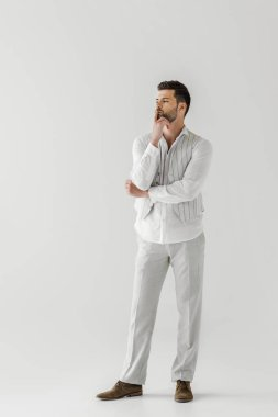 thoughtful man in linen clothes with finger on mouth isolated on grey background