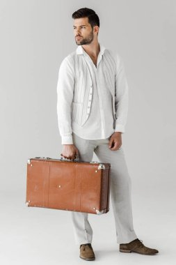 serious stylish male traveler in linen clothes holding vintage suitcase isolated on grey background