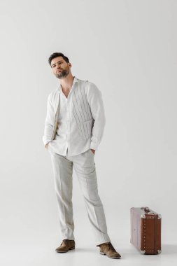 handsome man in linen clothes posing with hands in pockets near vintage suitcase isolated on grey background