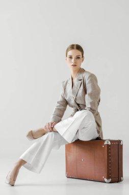 young stylish female tourist sitting on vintage suitcase isolated on grey background