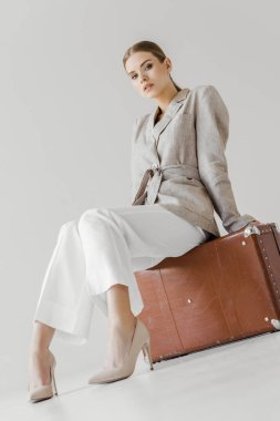 low angle view of stylish woman in linen jacket sitting on vintage suitcase isolated on grey background