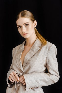 fashionable young woman in vintage jacket looking at camera isolated on black