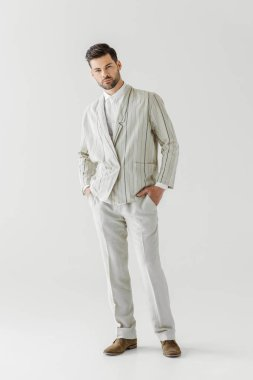 handsome young man in vintage stylish suit looking at camera on white