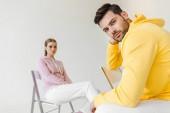 Stylový mladých modelek v růžové a žluté Mikiny sedí na židlích, izolované na bílém