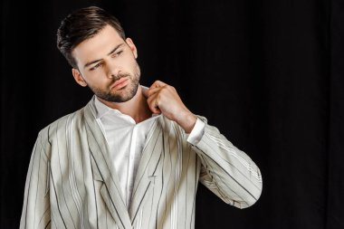 attractive young man in stylish striped jacket isolated on black