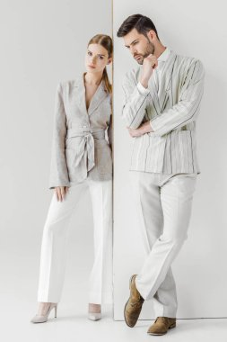 young male and female models in vintage jackets standing on white
