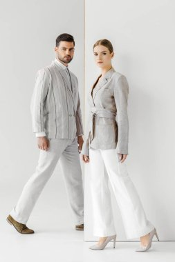 young male and female models in vintage clothes walking and looking at camera on white