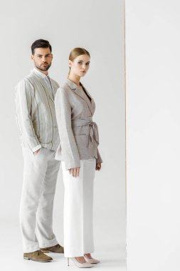 young male and female models in vintage clothes looking at camera on white