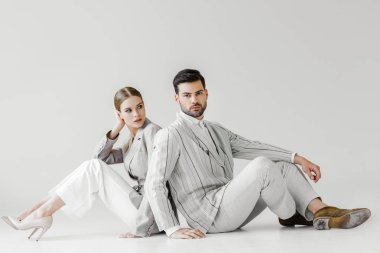 couple of attractive models in vintage clothes sitting on floor and leaning back to back on white