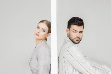 side view of attractive couple of models in stylish jackets leaning back on sides of wall on white