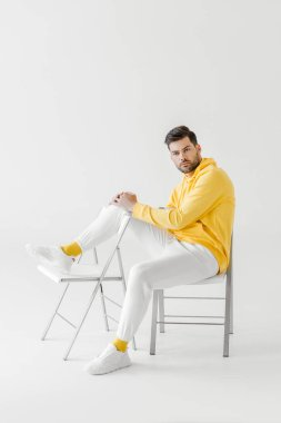 Attractive young man in yellow hoodie sitting on chairs on white stock vector